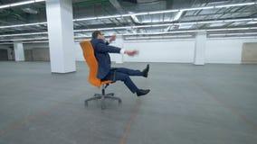 L'homme dans un costume dupe autour tout en se reposant dans une chaise de roulement banque de vidéos