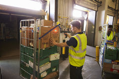 L'homme dans un entrepôt tient et balaye une boîte pour la livraison images libres de droits