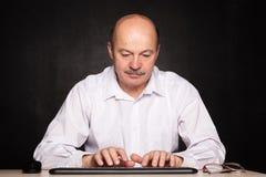L'homme dans une chemise blanche travaille à l'ordinateur, dactylographiant le texte sur le keybo Images stock