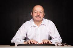 L'homme dans une chemise blanche travaille à l'ordinateur, dactylographiant le texte sur le keybo Photographie stock