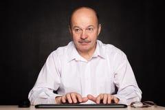 L'homme dans une chemise blanche travaille à l'ordinateur, dactylographiant le texte sur le keybo Photo libre de droits