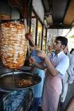 L'homme découpe le chiche-kebab en tranches de doner Images libres de droits