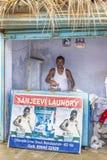 L'homme de blanchisserie pose à sa boutique avec l'affiche Photos libres de droits