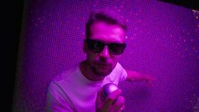 L'homme de brune utilisant les lunettes de soleil et le T-shirt blanc chante tenir le microphone clips vidéos