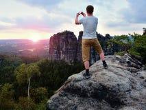 L'homme de cheveux courts sur la falaise de la roche prend la photo Soirée ensoleillée en montagnes rocheuses Photographie stock