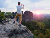 L'homme de cheveux courts sur la falaise de la roche prend la photo Soirée ensoleillée en montagnes rocheuses Images libres de droits