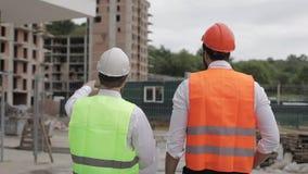 L'homme de constructeur et d'architecte discutent le plan de construction du centre moderne d'affaires presque se tenant banque de vidéos