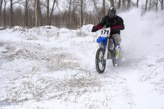 L'homme de coureur de sportif accomplit un tour rapide sur une moto sur l'extrémité de route La voie de course est très inégale image libre de droits