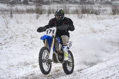 L'homme de coureur de sportif accomplit un tour rapide sur une moto sur l'extrémité de route La voie de course est très inégale photos libres de droits