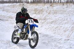 L'homme de coureur de sportif accomplit un tour rapide sur une moto sur l'extrémité de route La voie de course est très inégale image stock