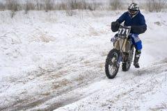 L'homme de coureur de sportif accomplit un tour rapide sur une moto sur l'extrémité de route La voie de course est très inégale photo libre de droits