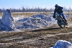 L'homme de coureur de sportif accomplit un tour rapide sur une moto sur l'extrémité de route La voie de course est très inégale photo stock