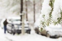 L'homme de fond nettoie une voiture de la première neige pendant l'hiver dans le pays Images libres de droits
