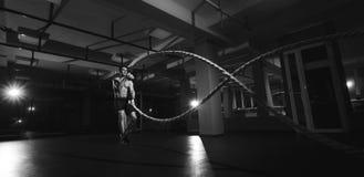 L'homme de forme physique établissant avec la bataille ropes à un gymnase Image libre de droits