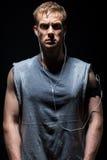 L'homme de forme physique dans la chemise sans manche grise sue et regarde photo stock