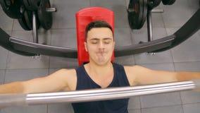 L'homme de forme physique dans le coffre de formation de gymnase muscles faisant le banc à presse plat avec le barbell banque de vidéos