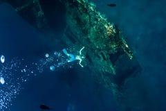 L'homme de Freediver font des bulles au naufrage sous-marin photographie stock libre de droits