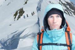 L'homme de grimpeur se tient en montagnes d'hiver, surfeurs marchant vers le haut pour le freeride à l'arrière-plan Images libres de droits