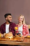 L'homme de jeune femme et d'hispanique s'asseyant en café tiennent Juice Order Beef Burger Served orange en papier sur le Tableau Photos stock