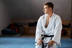 L'homme de karaté dans le kimono s'assied sur des genoux sur le plancher dans le gymnase d'arts martiaux photographie stock