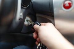 L'homme de la main s branchent une clé mettant en marche le moteur d'une voiture Images stock