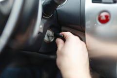 L'homme de la main s branchent une clé mettant en marche le moteur d'une voiture La main Image stock