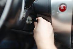 L'homme de la main s branchent une clé mettant en marche le moteur d'une voiture Photos libres de droits