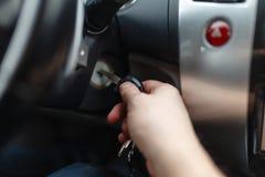 L'homme de la main s branchent une clé mettant en marche le moteur d'une voiture Images libres de droits
