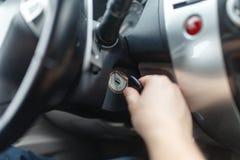 L'homme de la main s branchent une clé mettant en marche le moteur d'une voiture Photo libre de droits