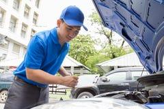 L'homme de mécanicien tenant le presse-papiers et vérifient la voiture Photographie stock