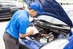 L'homme de mécanicien tenant le presse-papiers et vérifient la voiture Image stock