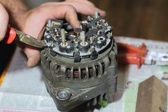 L'homme de maître répare le vieux générateur de voiture à la maison images libres de droits