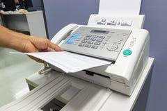 L'homme de main utilisent un télécopieur dans le bureau images libres de droits