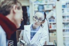 L'homme de maladie achète un médicament dans la pharmacie photo stock