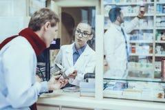 L'homme de maladie achète un médicament dans la pharmacie image stock