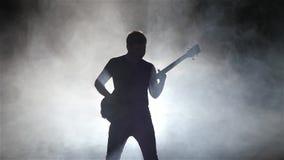 L'homme de musicien dans un studio fumeux joue autoritaire la guitare basse banque de vidéos