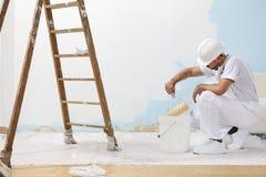 L'homme de peintre au travail prend la couleur avec le rouleau de peinture du b Photo libre de droits