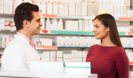 L'homme de pharmacien dans la pharmacie communique avec le visiteur Photographie stock libre de droits