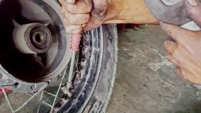 L'homme de plan rapproché commande la pression dans le pneu avec le manomètre dans la boutique banque de vidéos