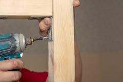 L'homme de plan rapproché travaille avec le tournevis tenu dans la main de batterie sur la surface en bois image stock