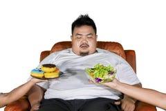L'homme de poids excessif confus choisit la salade ou des butées toriques image stock