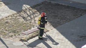 L'homme de pompier met dessus l'équipement et l'équipement du feu avant de commencer le travail, formation, exercices, profession clips vidéos