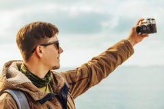 L'homme de randonneur prend l'autoportrait de photographies avec la came de photo de vintage Photographie stock libre de droits