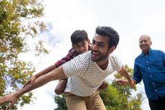 L'homme de regard première génération heureux donnant le ferroutage au fils Photo libre de droits