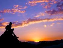 L'homme de silhouette s'asseyent au-dessus de la montagne Photos libres de droits
