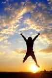 L'homme de silhouette sautent par-dessus le coucher du soleil Photo stock