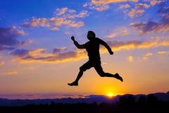 L'homme de silhouette sautent par-dessus le coucher du soleil Photos stock