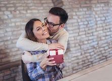 L'homme de sourire étonne son amie avec le présent à la maison Photos libres de droits