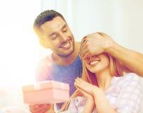 L'homme de sourire étonne son amie avec le présent Image libre de droits