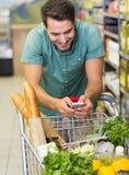 L'homme de sourire achètent des produits et employer son smaprtphone photos stock